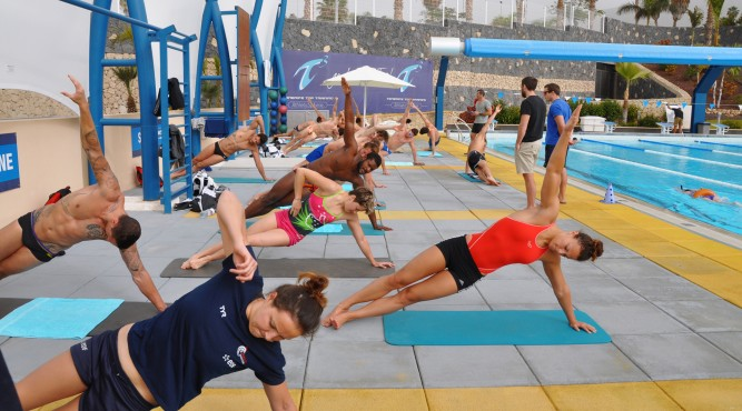 group doing side-planks at the pool