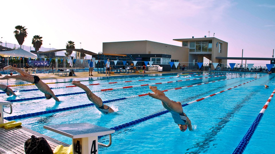 Swimcamp Wateraddict athletes jumping in the 50 Meter pool of Tenerife Top Training. the Biulding and cafeteria in the Background. Click here to check out swimming at Tenerife Top Training in Spain