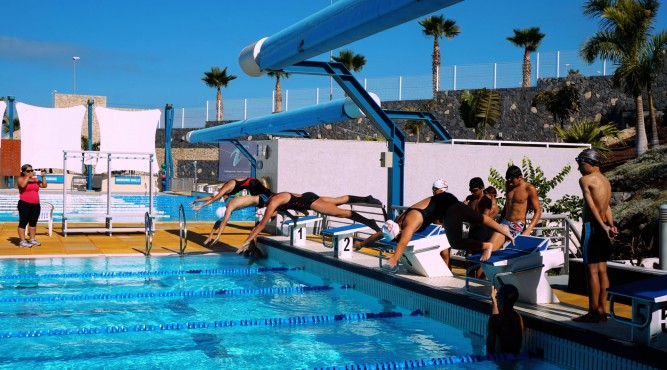 athletes jumping in the 25 meter pool. Check out our swimming camps to be next.