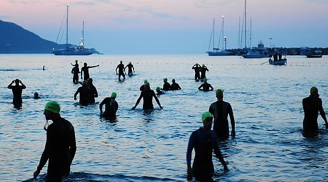 athletes walking out the ocean after triathlon training