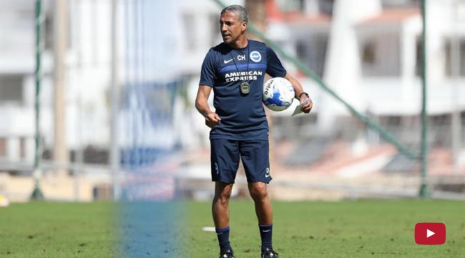 A coach is holding a ball, while he gives instructions too his team. This video shows a football trainingsession at Tenerife Top Training