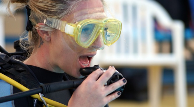 A female wheelchair tennis Player wearing a diving mask and takes the mouthpiece of diving equipment in the mouth