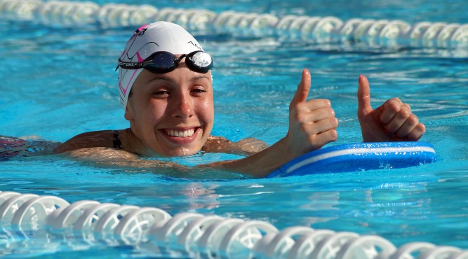 Modern Pentathlon Athlete is swimming in the olympic pool. She is using a swimming kickboard and and raises both thumbs
