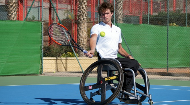 Nico Langmann sits in his wheelchair, swinging the tennis racket and focuses the tennis ball infront of him
