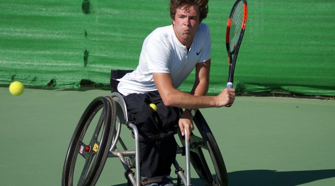 Nico Langmann a wheelchair tennis player swings his racket with the right hand. With the left he holds the wheelchair to stabilize himself. The Mouth is closed and the eyes are wide opened focusing the Ball which comes from the left.