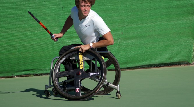 Nico Langmann sits in his wheelchair, holding the tennis racket and waiting for the ball