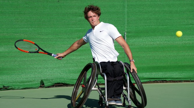 Nico Langmann a wheelchair tennis player swings his racket and is waiting of ball to hit it