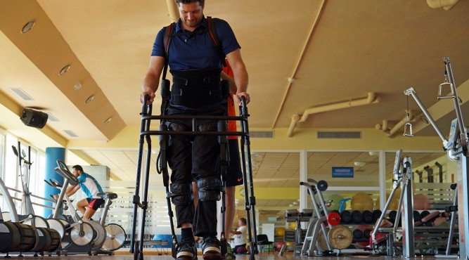 Disabled Male Tennis Player is walking with a special construction in the gym of T3. He is very focused and looks down to his feets