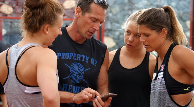 The Trainer explains and shows Viktoria Schwarz and two other girls the training schedule in der CrossFit Box