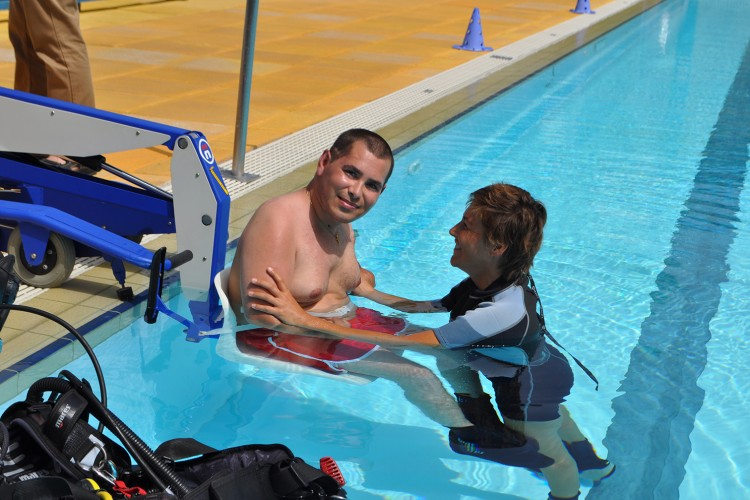 disabled athlete sits in the pool-lift and a coach helps him to get in the water. check out our barrier-free sports