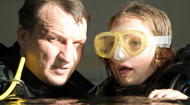 coach with young student learning how to dive