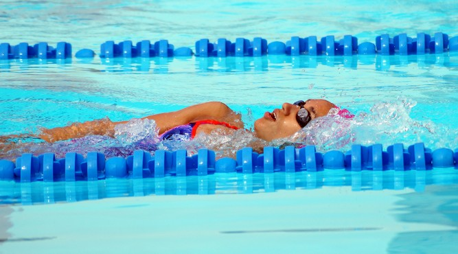 África is swimming between 2 blue lanes Backstroke during her swim training camp