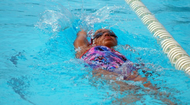 África Zamorano is swimming backstroke in the olympic pool of Tenerife Top Training. She is nearly complete under water but the face is visable.