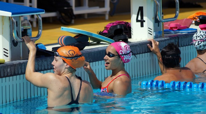 África Zamorano clings to the starting block of the Olympic pool and talks to another swimmer