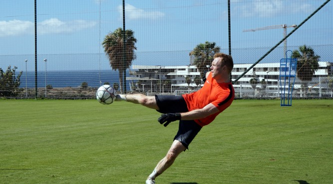 Lee Robinson kicks a football with his right foot. He is focusing the ball and this right is nearly horizontal.