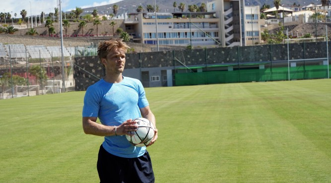 Mark Robinson is standing on the Football pitch. In the Background is the building of Tenerife Top Training. He is holding a football and looks where he can throw it.