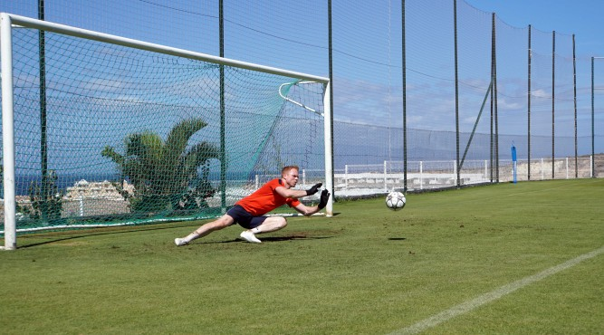 Lee Robinson stands in the center of the football goal. He is jumping to his left side and what to catch the ball which is 1 meter in front of him