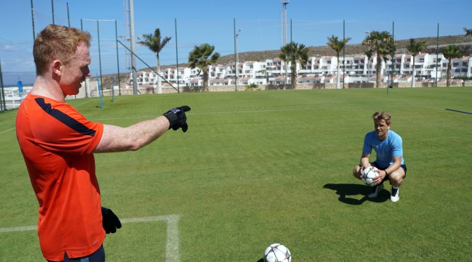 Lee Robinson stands and points with his right hand to his brother Mark Robinson who is squatting. He holds a football.