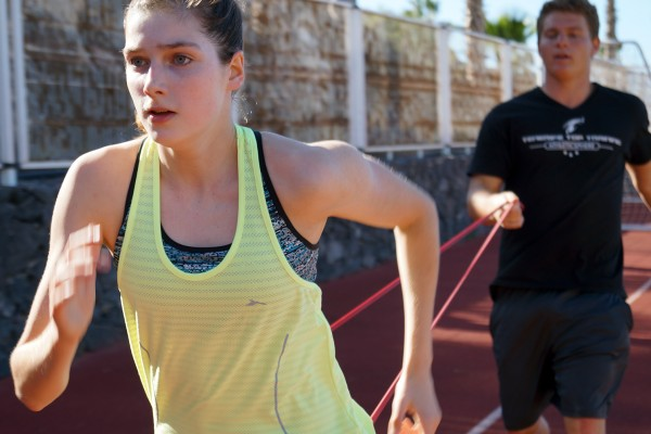 Personal trainer Lukas Brandmeier holds a band and the athlete is trying to run as fast as she can