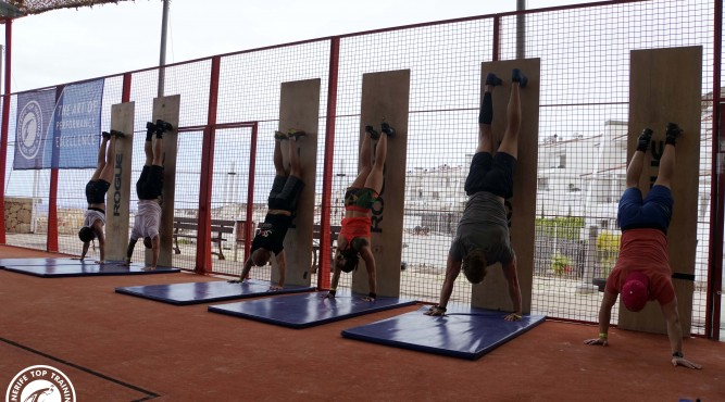 Six CrossFitter make some handstand push ups in the T3 outdoor Box