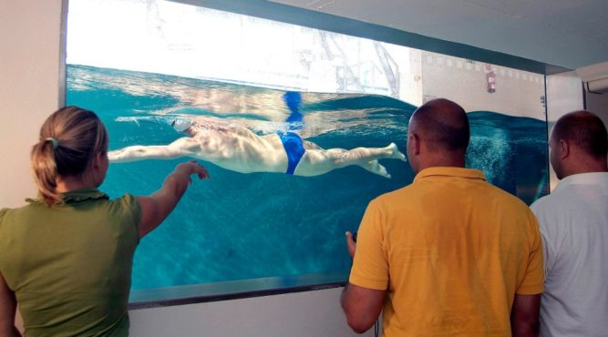 The athlete swims in the channel while his team analyzes his techniques